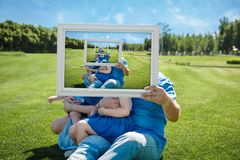Smiling family with children looking through an empty frame royalty free stock photos