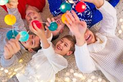 Smiling family at Christmas. Time holding Christmas lights while lying down Stock Images
