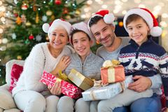 Smiling family at Christmas. Time holding lots of presents at home Royalty Free Stock Photography