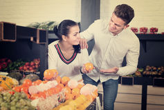 Smiling family couple examining various fruits Royalty Free Stock Photos