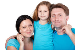 Smiling family, daughter in center hugs parents. Smiling family of three in blue shirts, little daughter in center hugs her parents Royalty Free Stock Photography