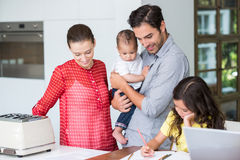 Smiling family with daughter studying at desk Royalty Free Stock Images