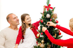 Smiling family decorating christmas tree at home. Family, holidays, generation and people concept - smiling family decorating christmas tree at home Stock Photos