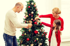 Smiling family decorating christmas tree at home Stock Images