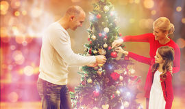 Smiling family decorating christmas tree at home. Family, holidays, generation and people concept - smiling family decorating christmas tree at home Royalty Free Stock Photo
