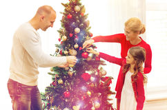 Smiling family decorating christmas tree at home. Family, holidays, generation and people concept - smiling family decorating christmas tree at home Stock Image