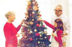 Smiling family decorating christmas tree at home. Family, holidays, generation and people concept - smiling family decorating christmas tree at home Stock Photo