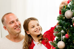 Smiling family decorating christmas tree at home. Family, holidays, generation and people concept - smiling girl with father decorating christmas tree at home Stock Images