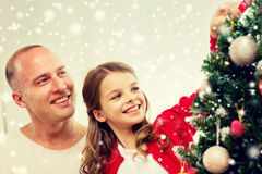 Smiling family decorating christmas tree at home. Family, holidays, generation and people concept - smiling girl with father decorating christmas tree at home Royalty Free Stock Image