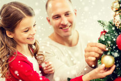 Smiling family decorating christmas tree at home. Family, holidays, generation and people concept - smiling girl with father decorating christmas tree at home Royalty Free Stock Images