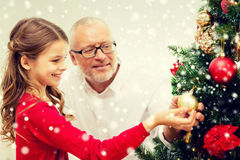 Smiling family decorating christmas tree at home. Family, holidays, generation and people concept - smiling girl with grandfather decorating christmas tree at Stock Photo