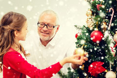Smiling family decorating christmas tree at home. Family, holidays, generation and people concept - smiling girl with grandfather decorating christmas tree at Royalty Free Stock Photo