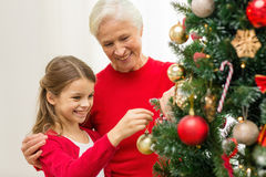 Smiling family decorating christmas tree at home. Family, holidays, generation and people concept - smiling girl with grandmother decorating christmas tree at Stock Photo
