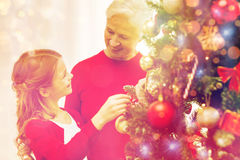 Smiling family decorating christmas tree at home. Family, holidays, generation and people concept - smiling girl with grandmother decorating christmas tree at Royalty Free Stock Image