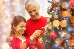 Smiling family decorating christmas tree at home. Family, holidays, generation and people concept - smiling girl with grandmother decorating christmas tree at Royalty Free Stock Photo
