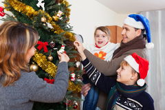 Smiling family decorating Christmas tree. At living room Stock Photo