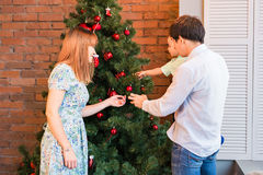 Smiling family decorating a Christmas tree in the living-room.  Stock Photo