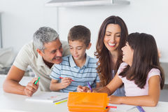 Smiling family drawing together in kitchen Royalty Free Stock Photos