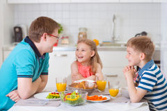 Smiling family eating breakfast in kitchen Stock Images