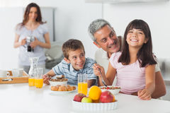 Smiling family eating breakfast in kitchen together Royalty Free Stock Photos