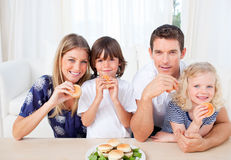 Smiling family eating burgers in the living room Stock Photo
