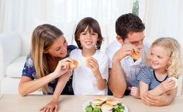 Smiling family eating burgers in the living room Stock Image