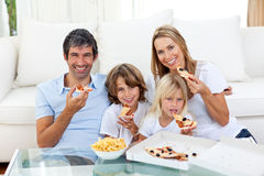 Smiling family eating a pizza sitting on the floor Stock Photo