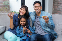 Smiling family eating pizza on the sofa Stock Images