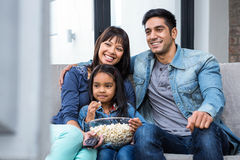 Smiling family eating popcorn while watching tv Stock Photography