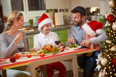 Family enjoying eating traditional Christmas dinner. Smiling family enjoying eating traditional Christmas dinner Royalty Free Stock Images