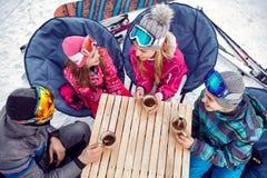 Family enjoying on hot drink at ski resort. Smiling family enjoying on hot drink at ski resort Royalty Free Stock Photos
