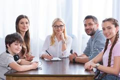 Smiling family and female counselor sitting at table on therapy session looking at camera. In office royalty free stock photo