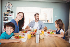 Smiling family with food on dining table Stock Photo