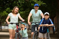 Smiling family of four with bicycles and scooter. In vacation at park Stock Images
