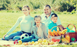 Smiling family of four having a picnic outdoors Royalty Free Stock Image