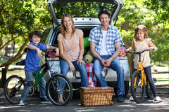 Smiling family in front of a car Stock Image