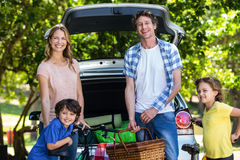 Smiling family in front of a car Stock Photos