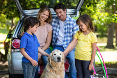 Smiling family in front of a car Royalty Free Stock Image