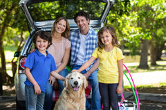 Smiling family in front of a car Royalty Free Stock Photo