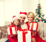Smiling family giving many gift boxes Royalty Free Stock Images