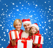 Smiling family giving many gift boxes Royalty Free Stock Photos