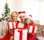 Smiling family giving many gift boxes Stock Photos