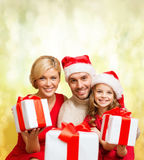 Smiling family giving many gift boxes Stock Photography