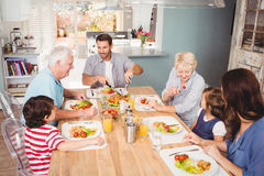 Smiling family with grandparents discussing at dining table Stock Photography