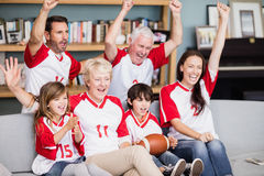 Smiling family with grandparents watching American football match Royalty Free Stock Images