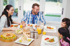 Smiling family having food while discussing at dining table Stock Photos