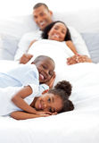 Smiling family having fun. Lying on a bed Royalty Free Stock Photos