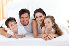 Smiling family having fun. Lying on the bed Stock Photo