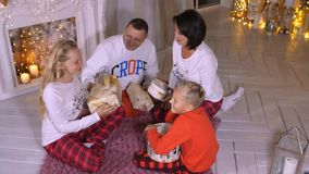 Smiling family having fun at Christmas eve and enjoying holiday gifts in cozy room. Happy family gifting New Year red stock video footage