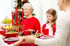Smiling family having holiday dinner at home. Family, holidays, generation, christmas and people concept - smiling family having dinner and praying at home Stock Photo